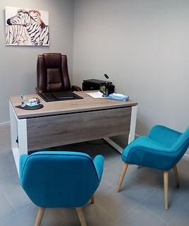 """Bureau avec deux sièges destinés aux patients et un siège pour la psychologue. Cadre mural """"zèbres""""."""