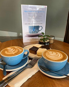 2 blue cups filled with coffee with a sign that says coffee for a cause