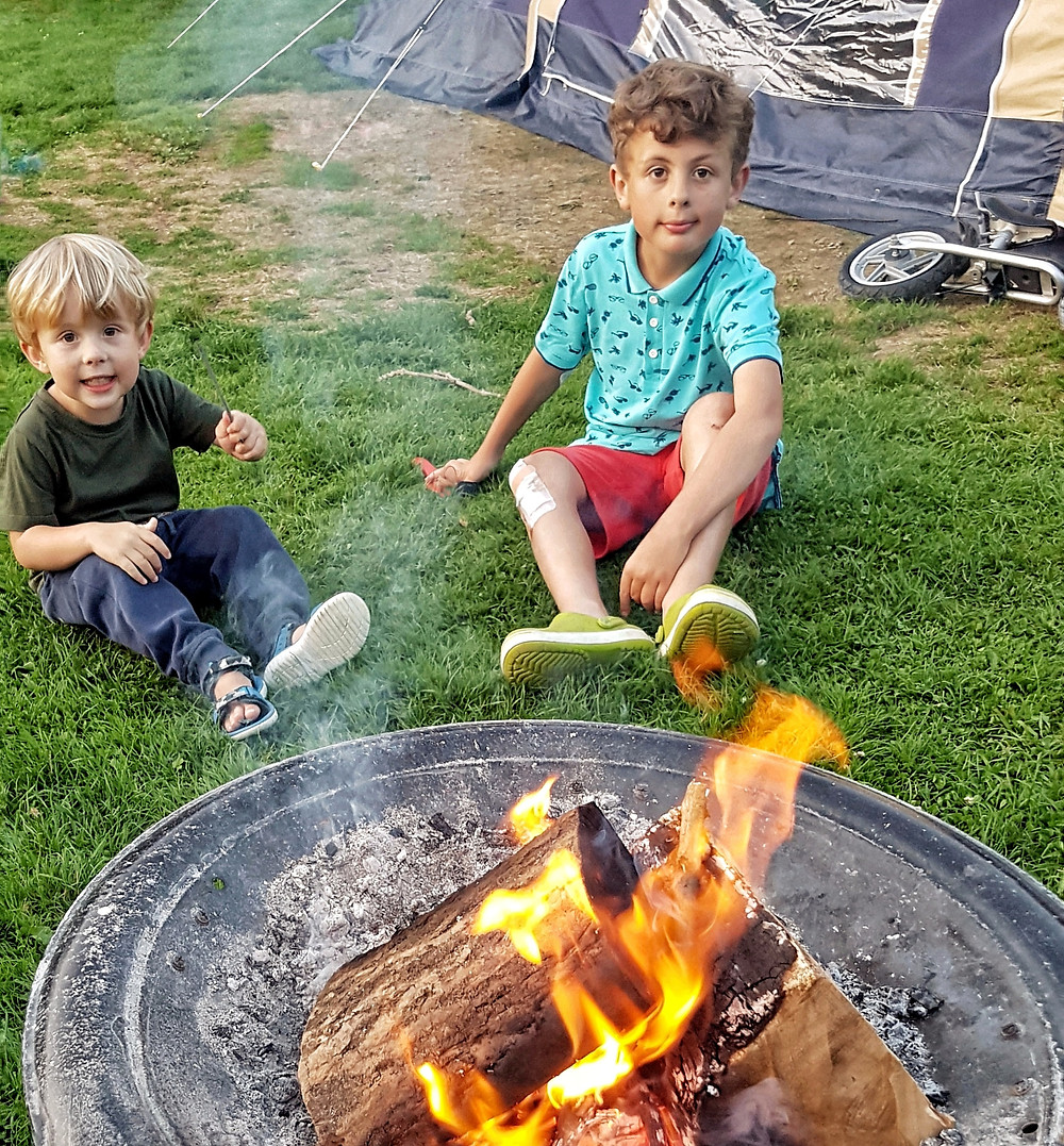 Children camping outdoors, sitting by campfire