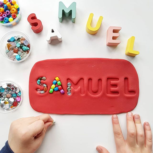name stamped in red playdough with loose parts