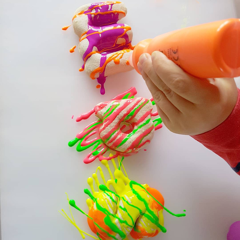 child painting letters orange