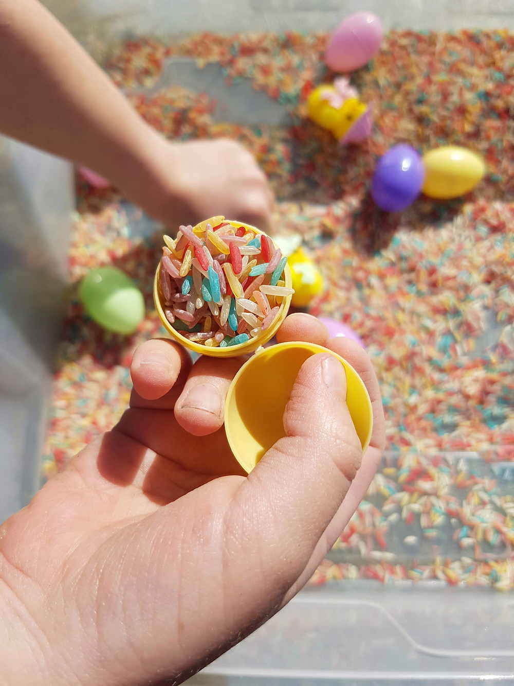 Close up of child playing with easter rice sensory bin