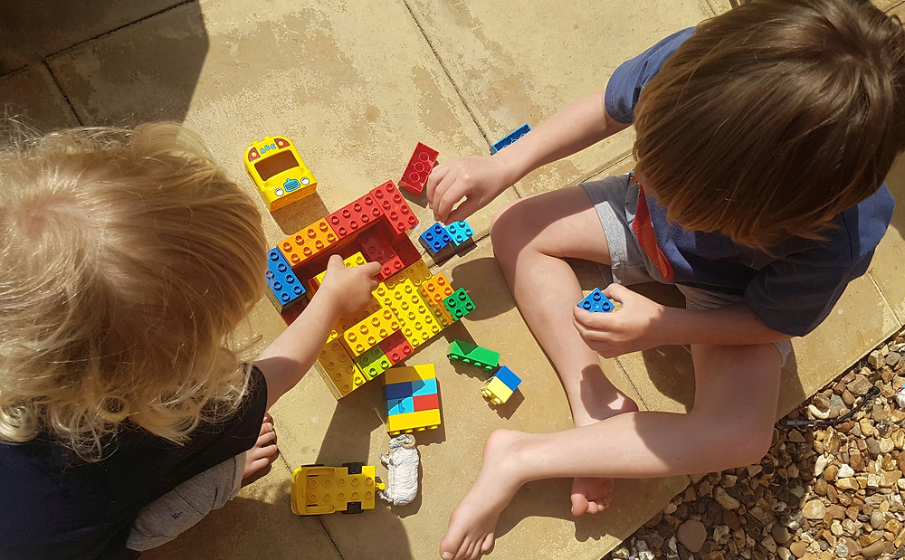 Two children playing with Lego Duplo on a patio outside