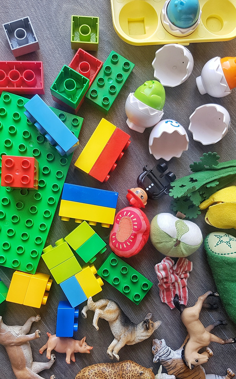 Colourful plastic toys, duplo, animals, tipped over the floor