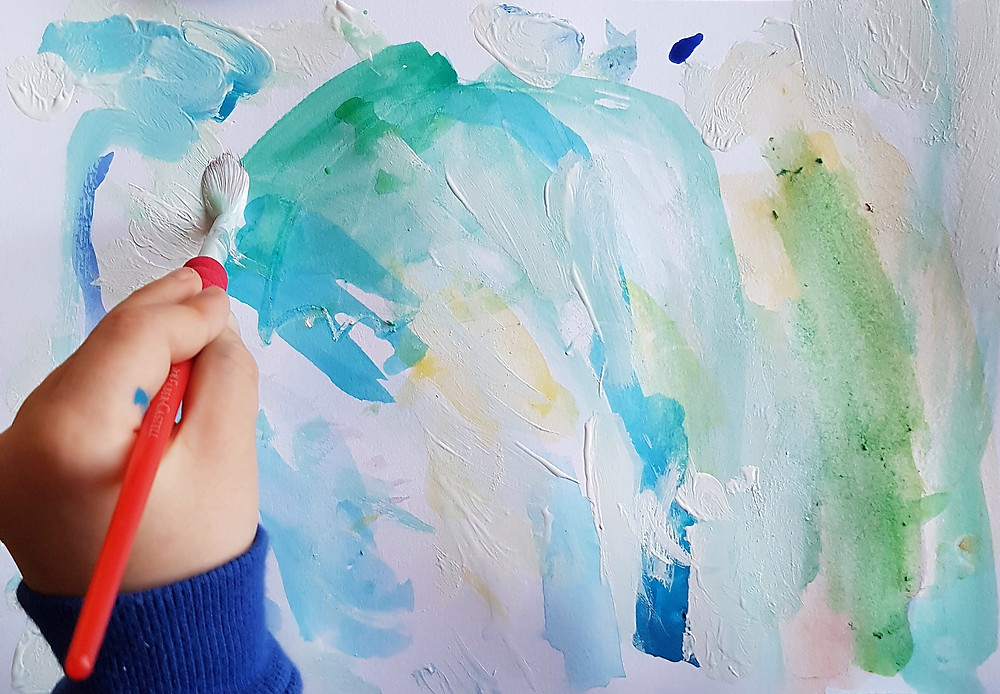 Child painting calming blue colours