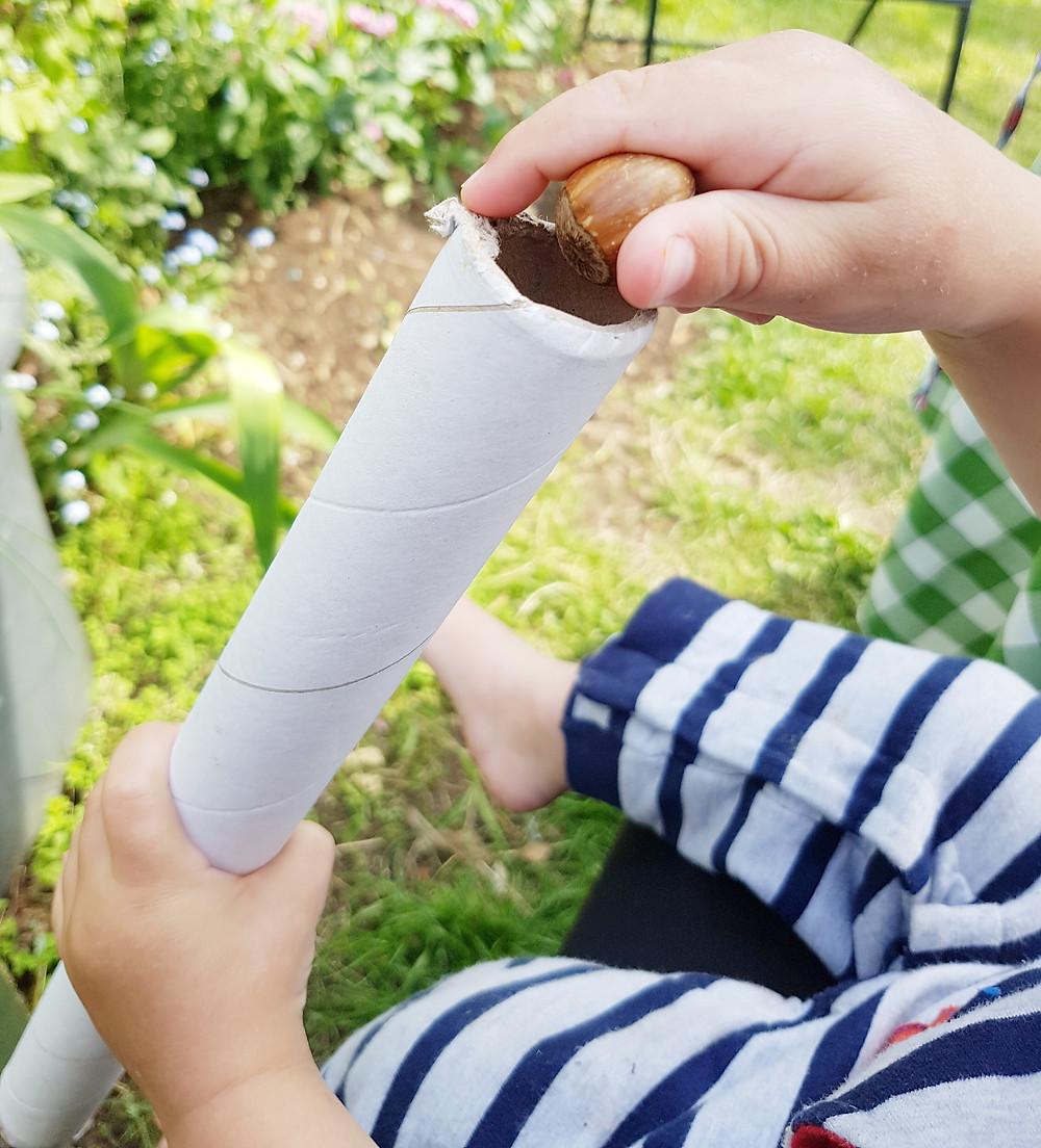 Loose parts play, baby enjoying how hazelnuts fall through a tube