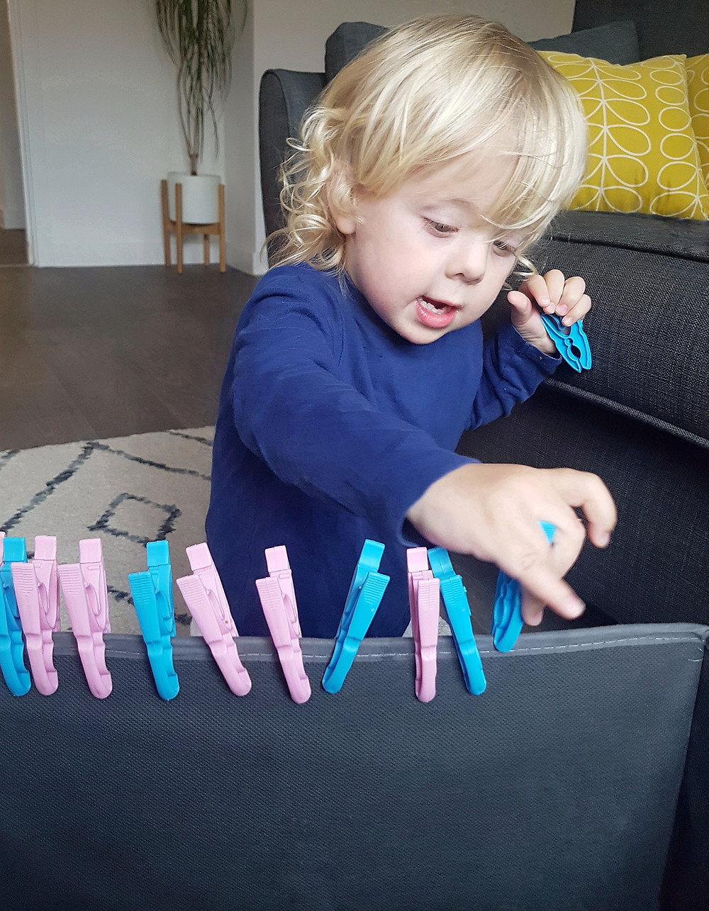 toddler playing with blue and pink pegs