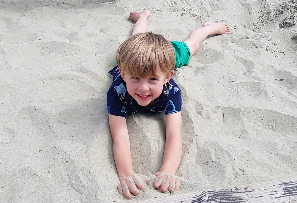 Child outdoors lying in sand