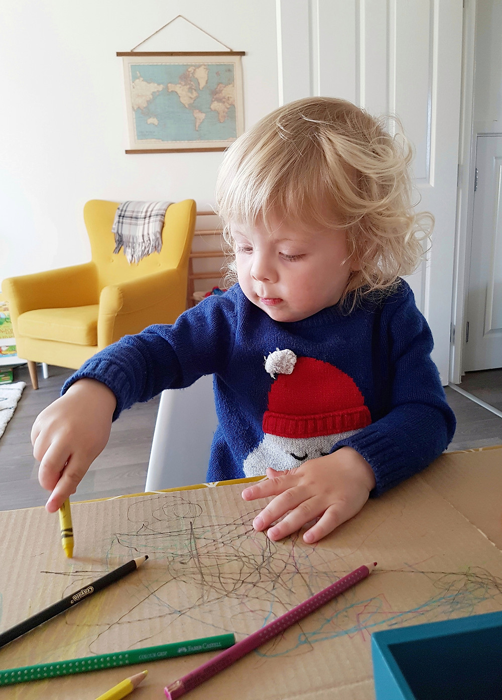 blonde toddler drawing on cardboard with yellow crayon