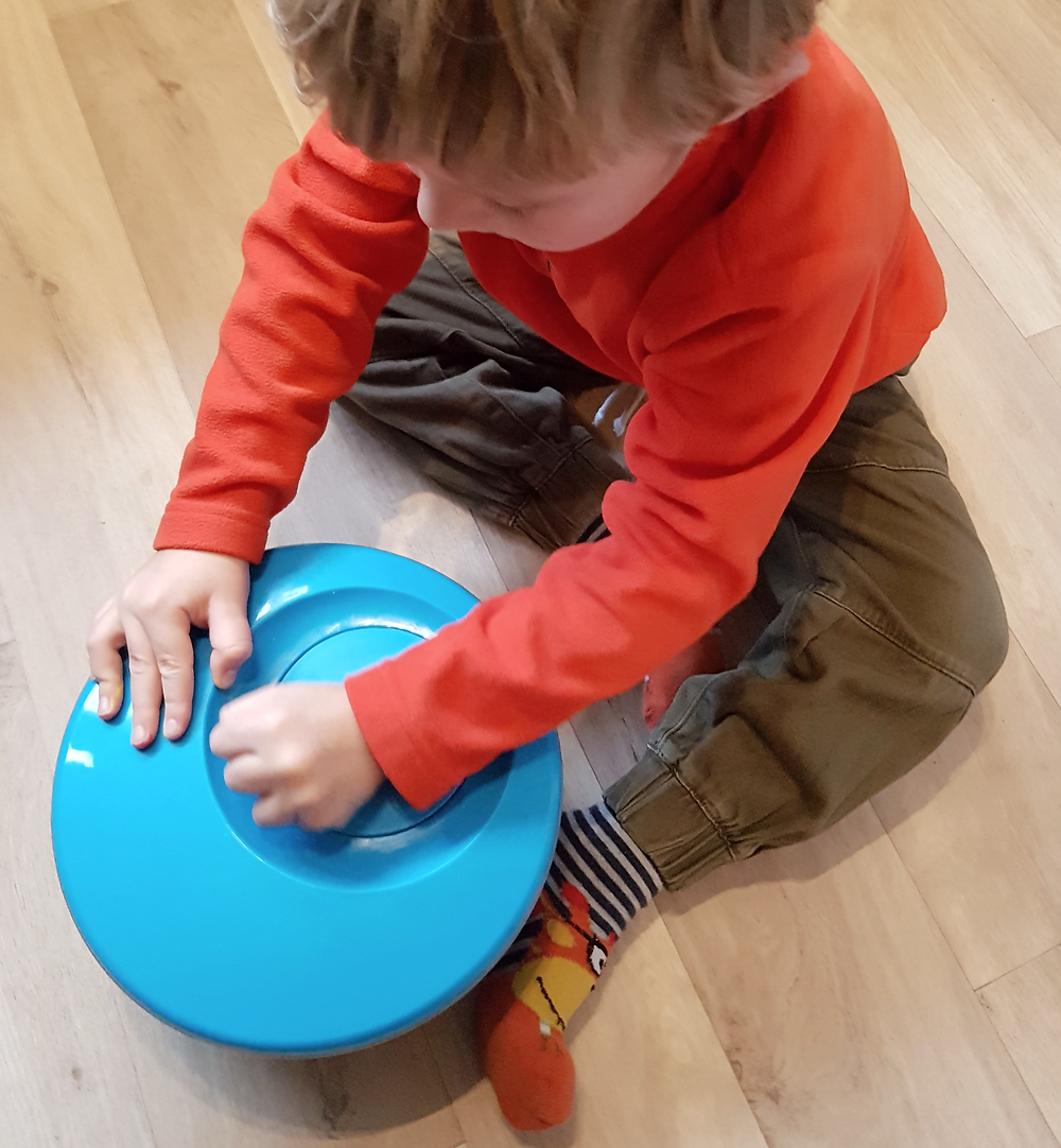 child using salad spinner for process art