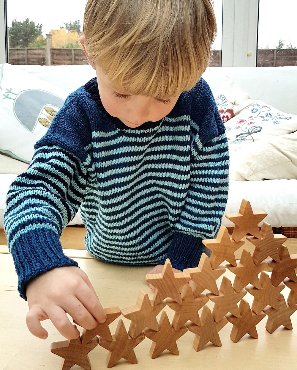Child in blue jumper stacking star toy