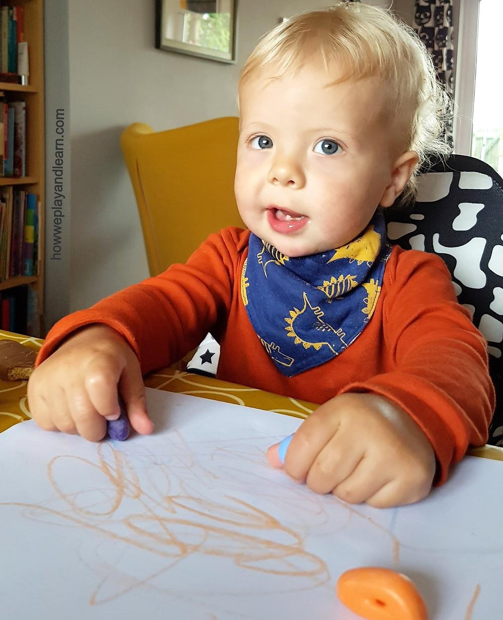 Blond toddler mark-making with Crayon Rocks