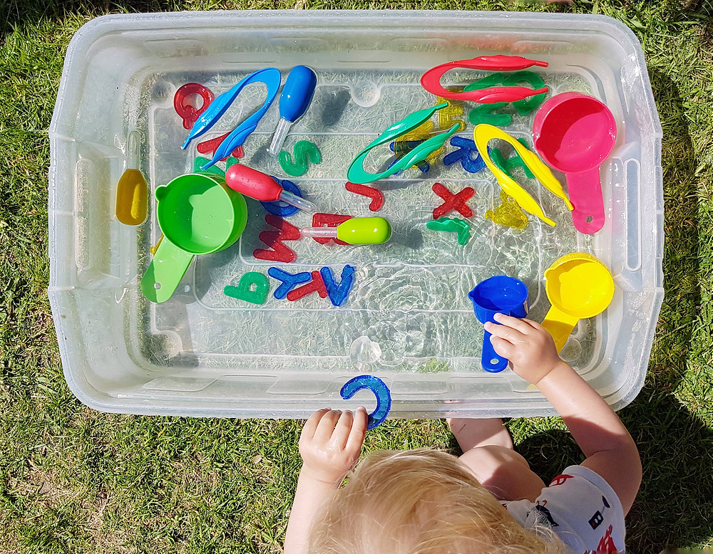 Baby and toddler colourful water play in a tub