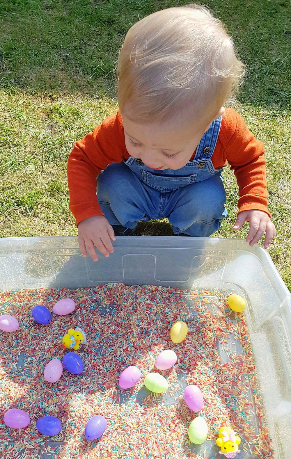 Child playing with easter rice sensory bin