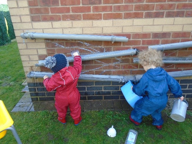 Pre-school children in red and blue rpuddlesuits playing with guttering