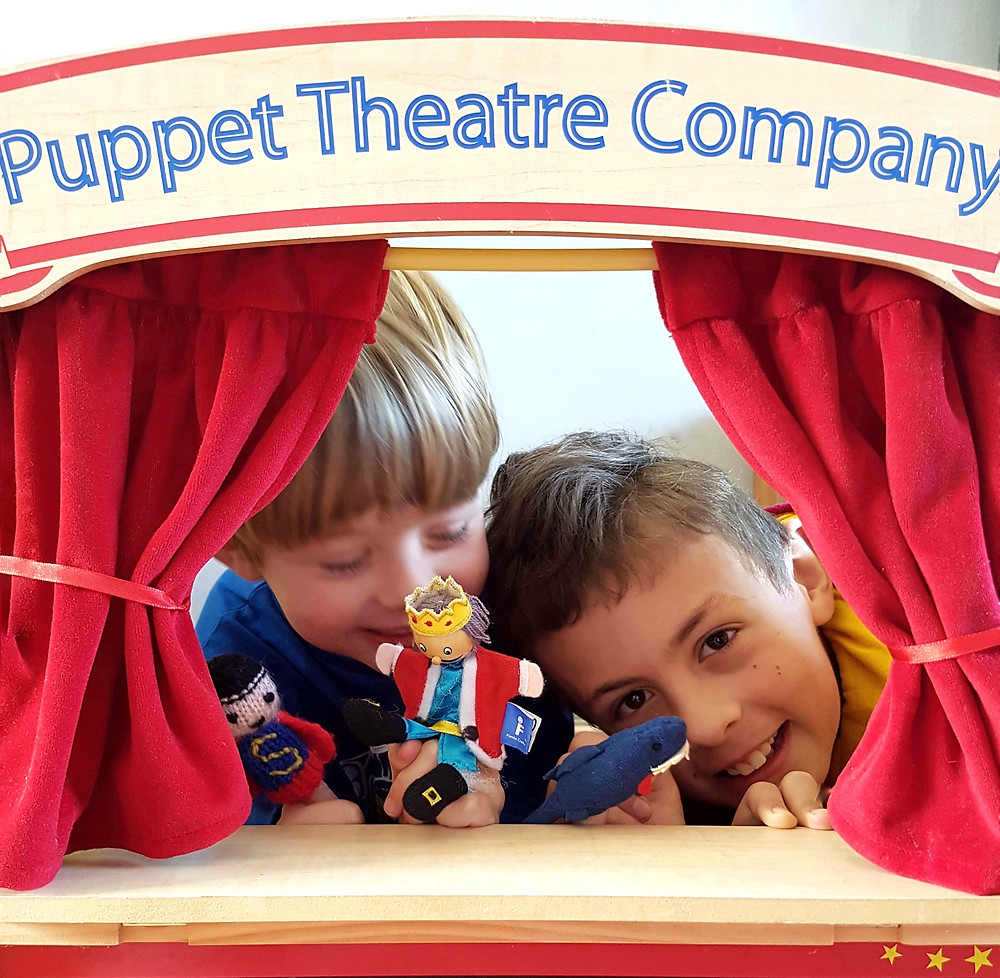 Two young children using a puppet theatre with read curtains