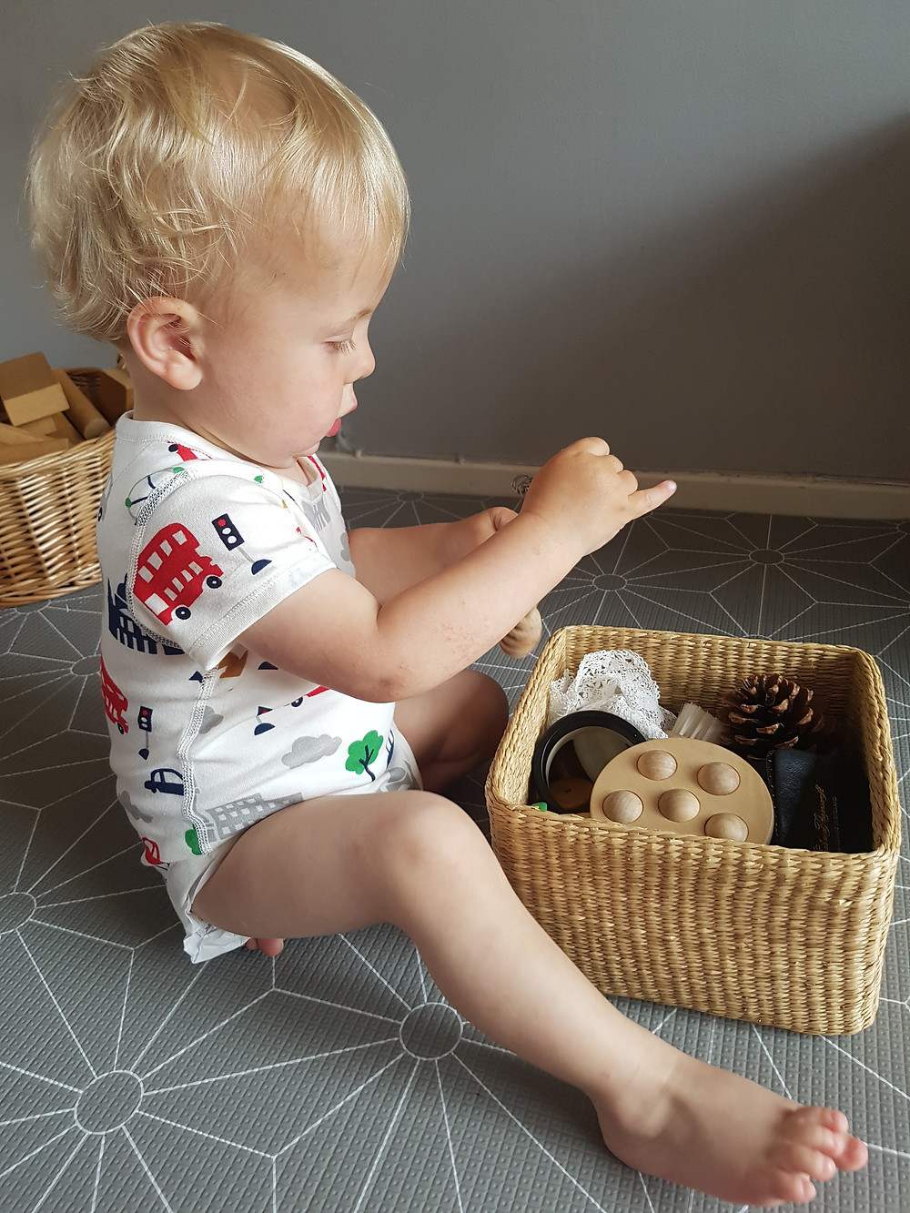 Baby in white romper playing with a treasure basket