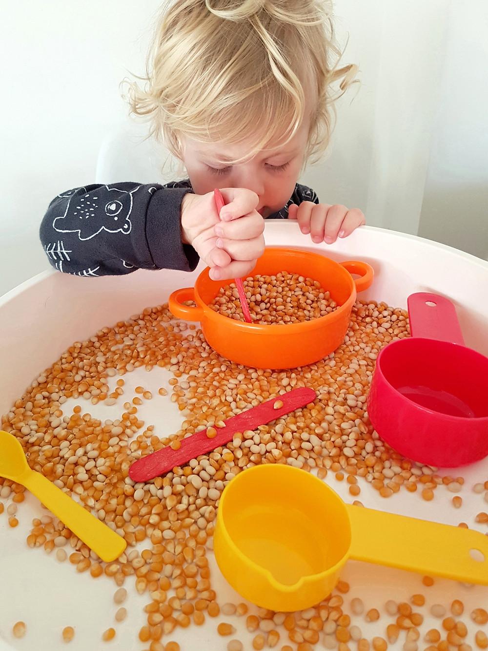 blonde toddler playing with corn sensory bin