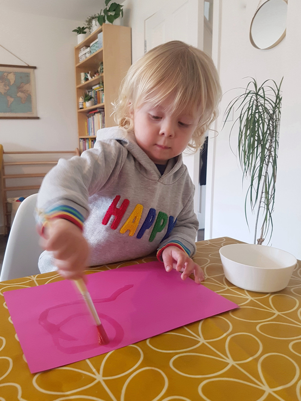 toddler painting on pink paper with water