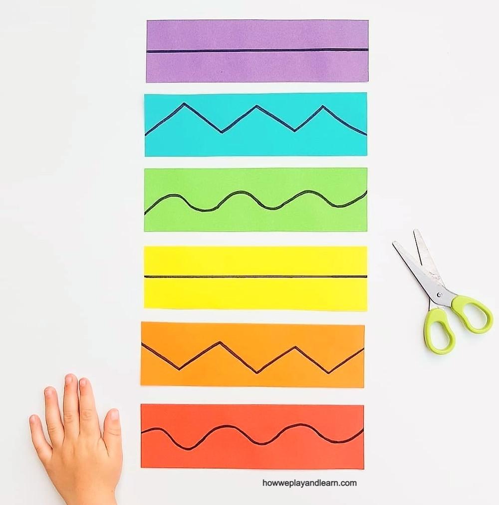 Childs hand, rainbow paper and scissors