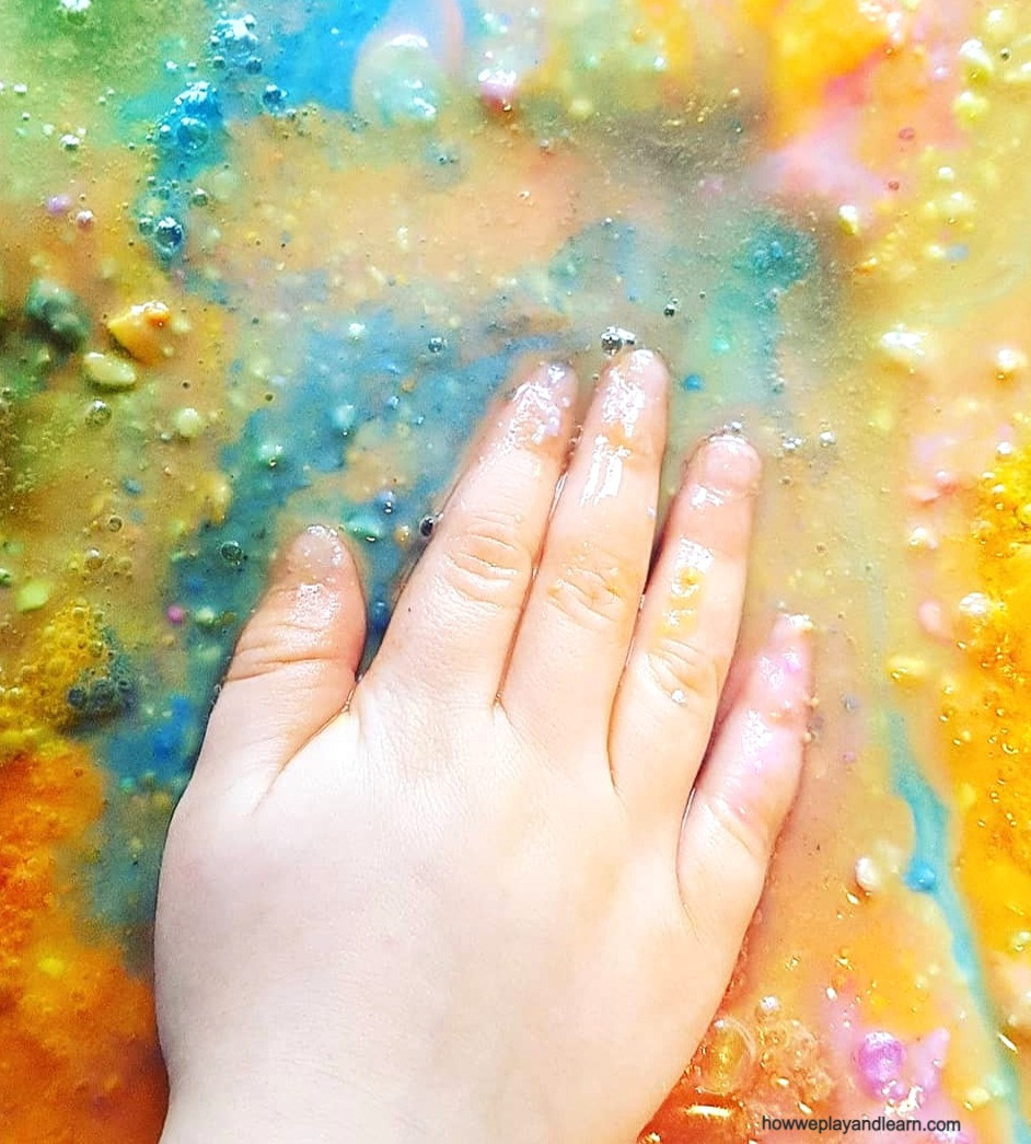 Child-s hand in rainbow coloured wet mess