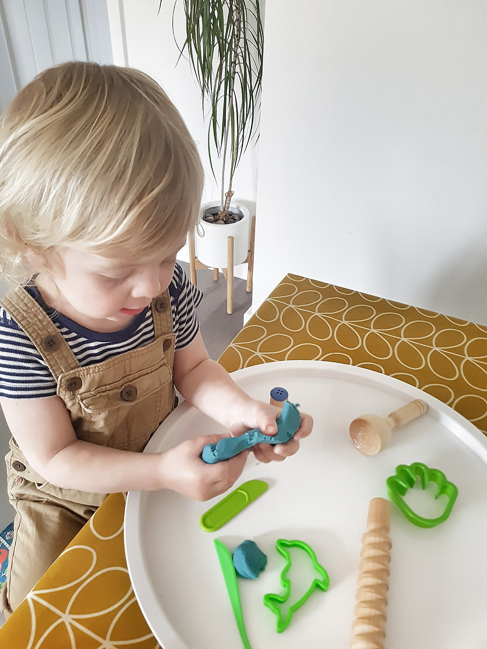 blond toddler playing with blue playdough at table