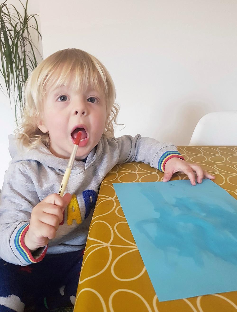 blonde toddler trying to eat paintbrush