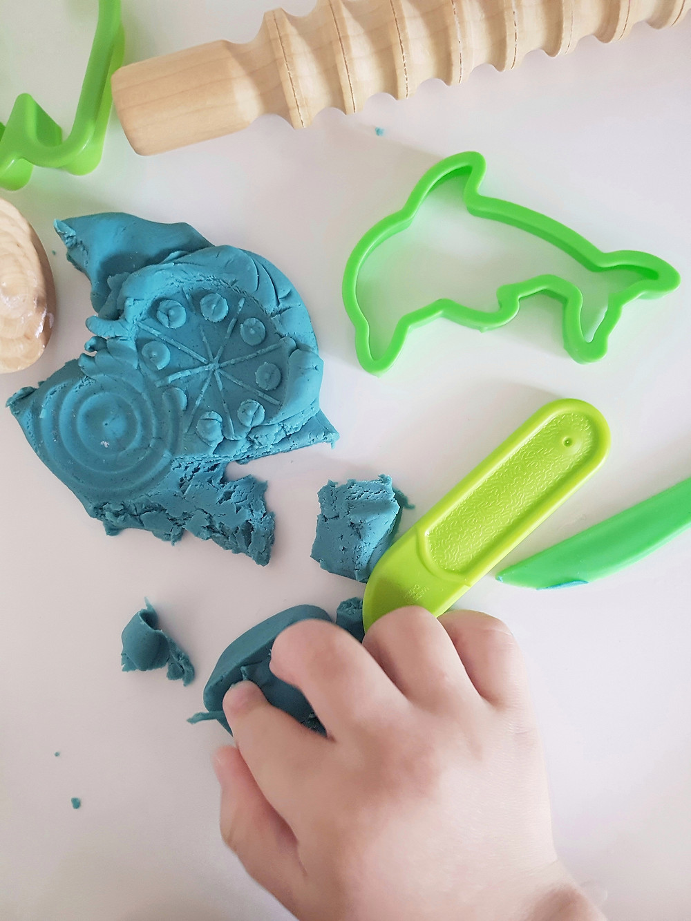 blue playdough with wooden rolling pin and green cutters