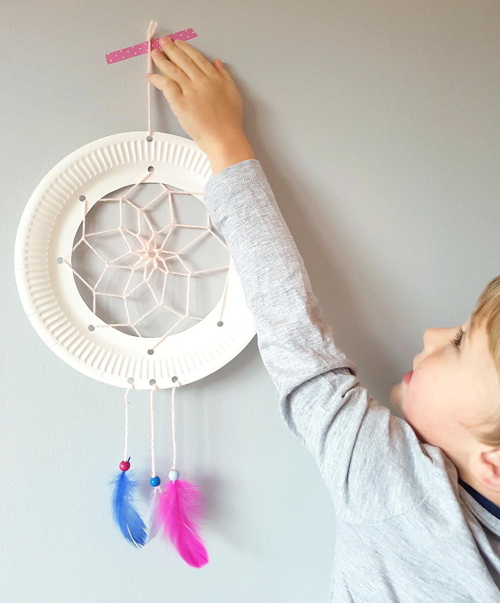 child hanging paper plate dreamcatcher craft on wall