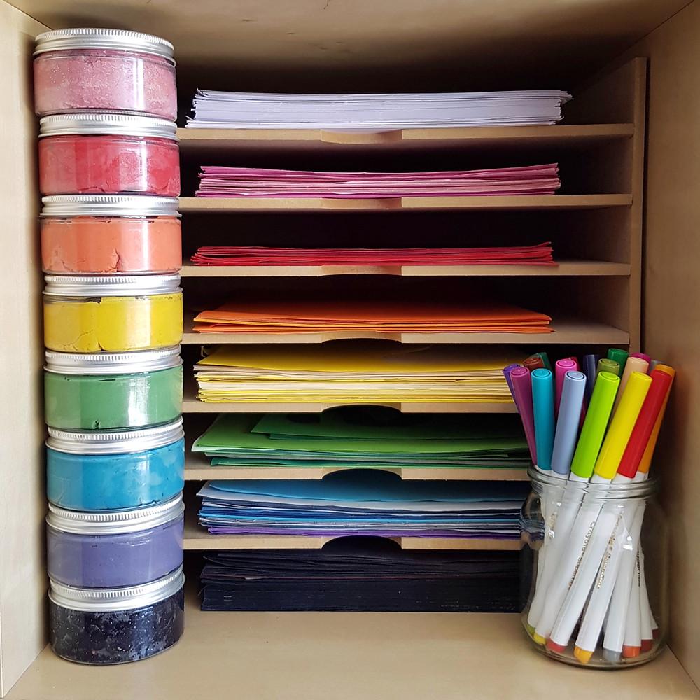 Rainbow coloured paper, pens and playdough