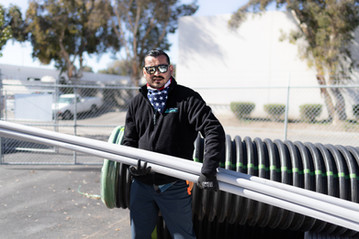 Aqua Flo employee holding pipe