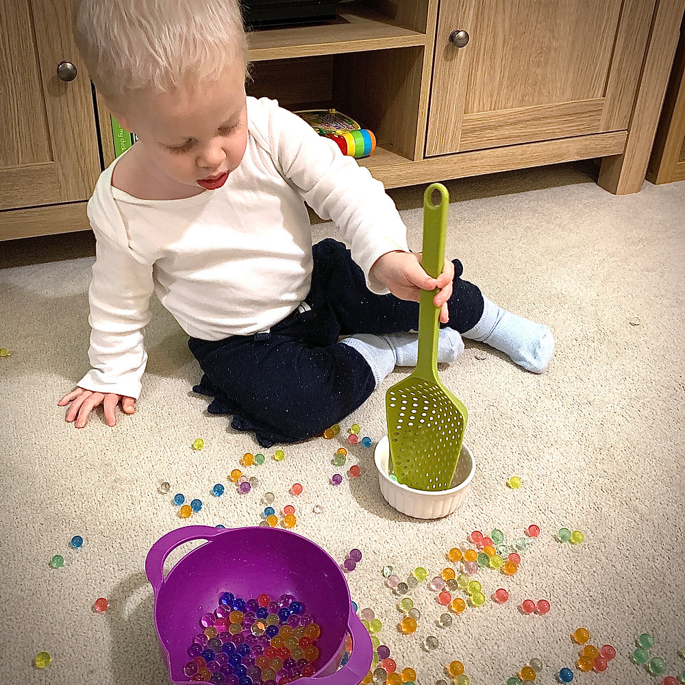 Joey playing with water beads with spoon and bowl