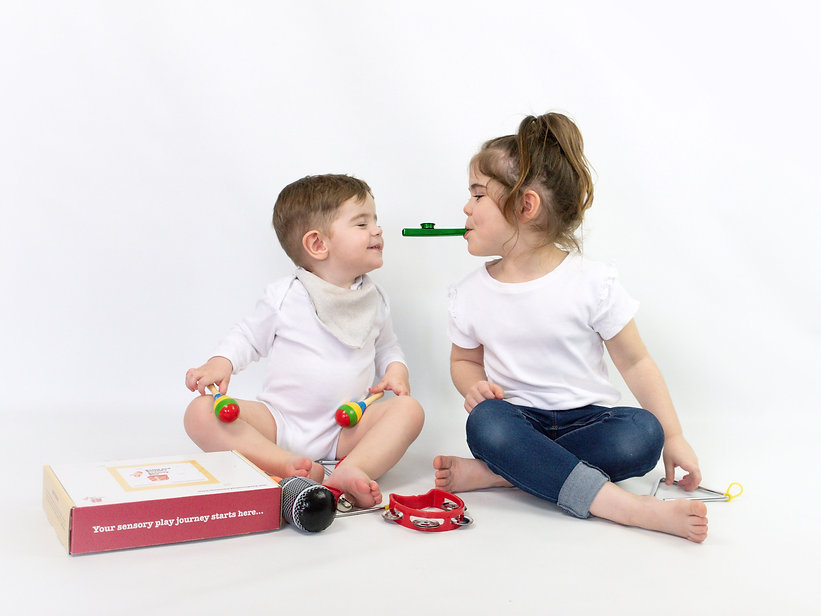 Two toddlers playing with sensory toy box