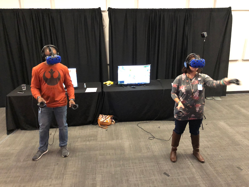 2 people trying virtual reality at an indoor event