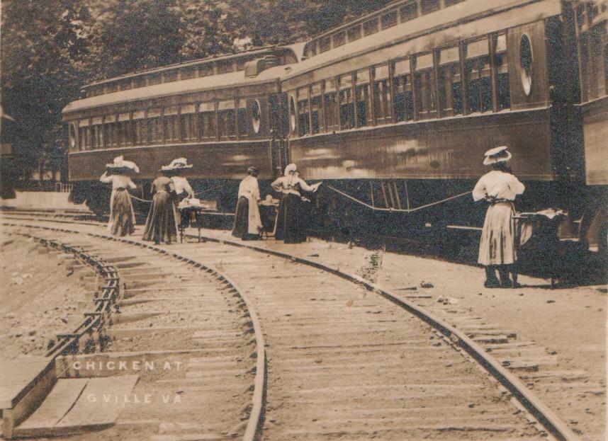 Ladies standing beside train cars serving food