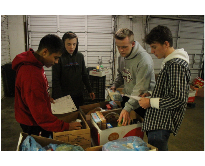 Samuel Collins, Landyn Spencer, Tanner Beaver, and Carson Barry work to sort boxes at Central Services.