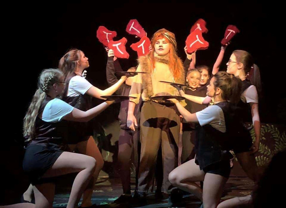 Sawyer Stacey, East High student, as Alex the Lion and Servers in ending pose of Steak.