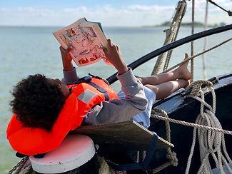 zion leest op het voordek met zijn rug t