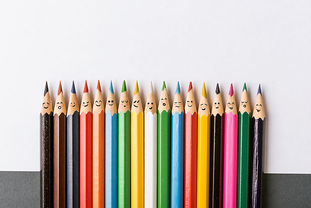 Color pencils with faces painted on them. the concept of a multinational family and equali