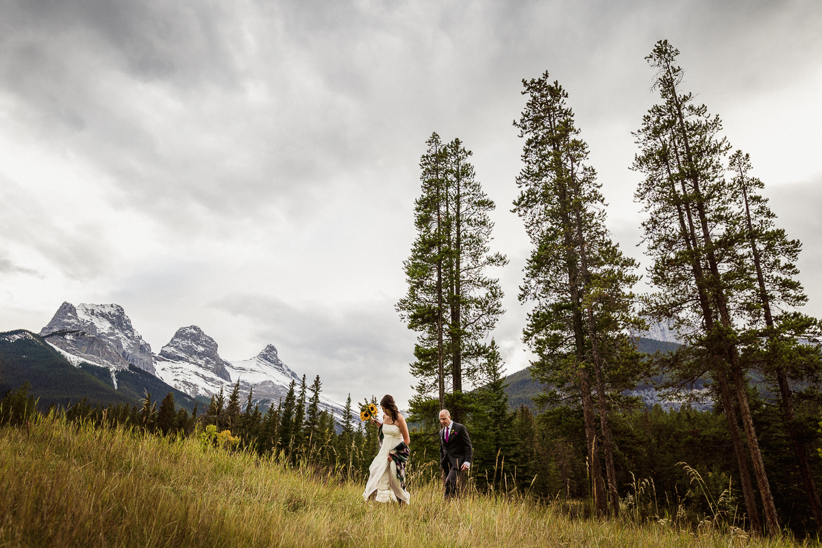 Walking in a field overlooking the Three Sisters in Canmore during this Canmore elopement