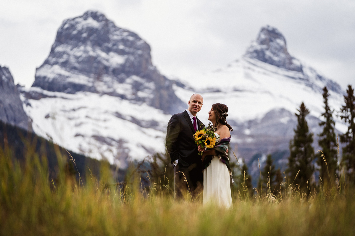 Bride and groom in a field overlooking the Three Sisters in Canmore