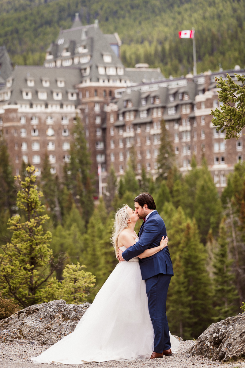 A kiss at Surprise Corner overlooking Banff Springs Hotel during this Banff elopement