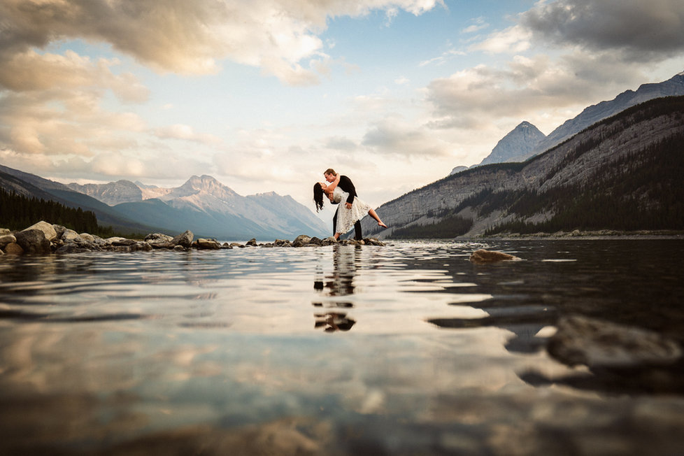 Romantic kiss by Canmore wedding photographer lake reflection