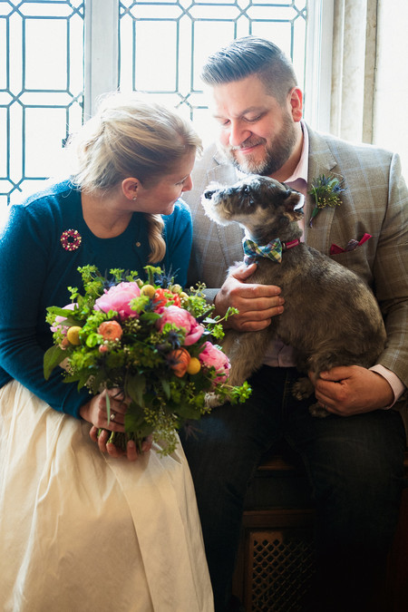 Candid photo of bride, groom and their dog right after they got married