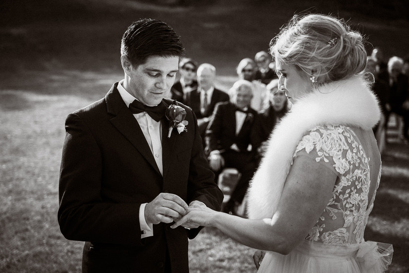 Placing the wedding ring on the bride's hand at Tunnel Mountain wedding in Banff