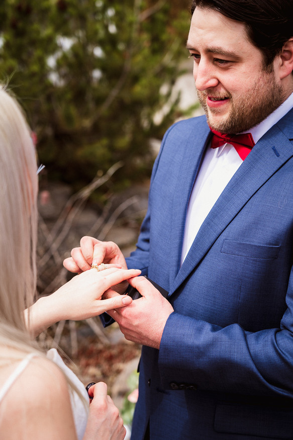Placing the ring on the finger during outdoor Banff elopement photography