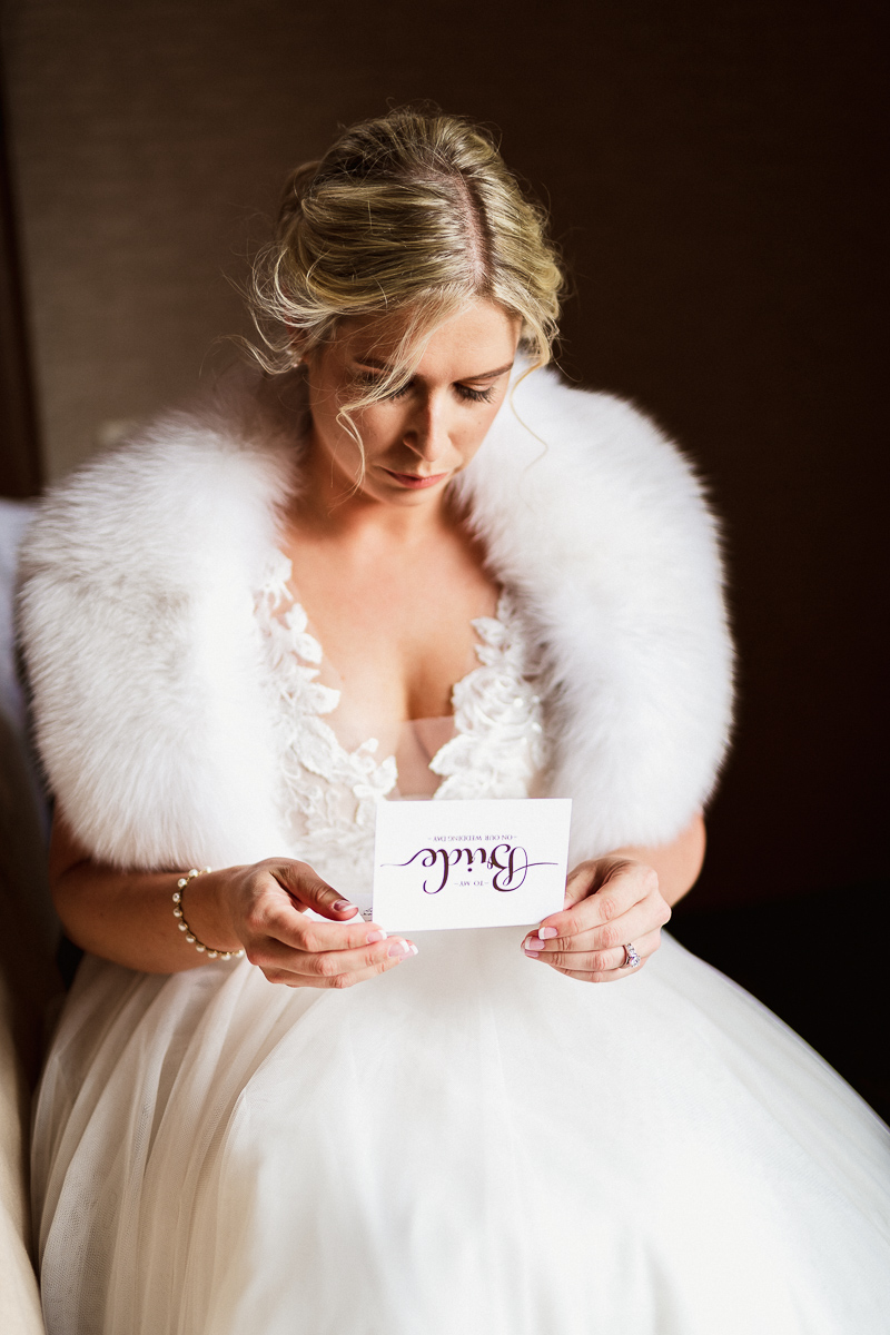 Bride reading letter from husband on wedding day, an emotional moment captured by Banff wedding photographer