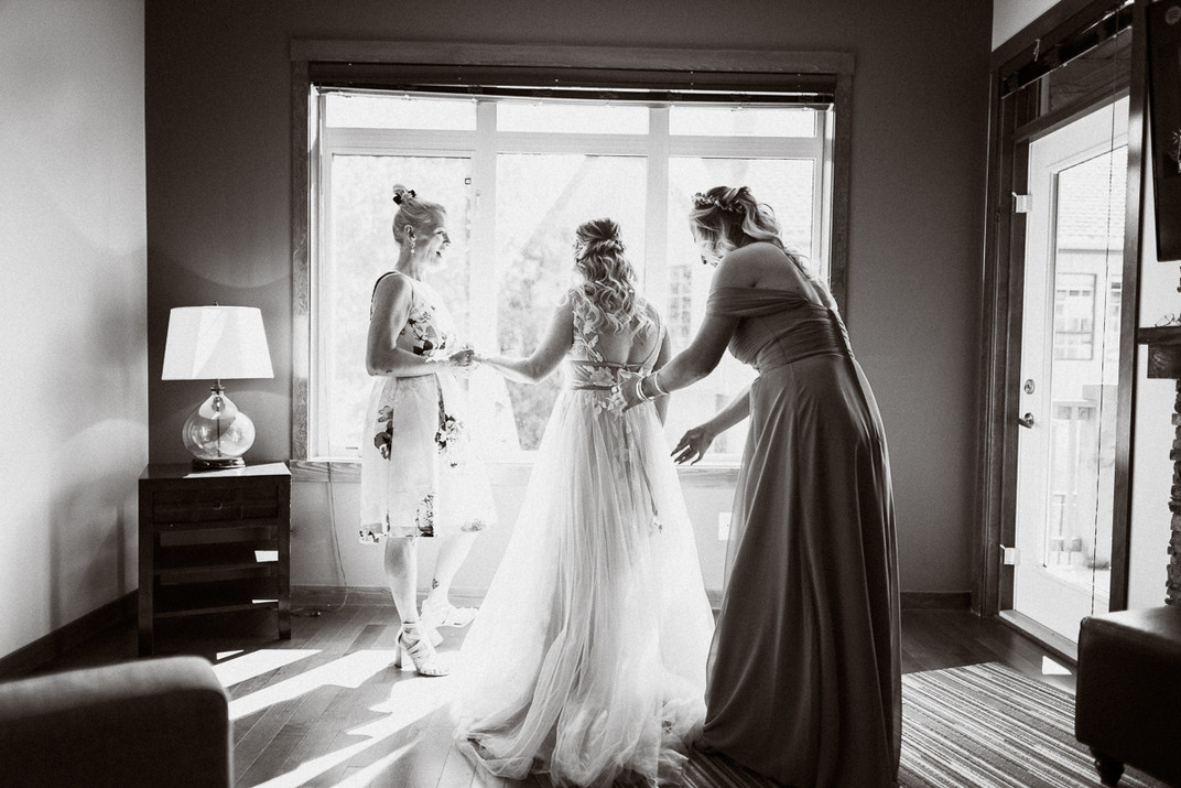 Bride's mother and bridesmaid helping with dress at Canmore wedding