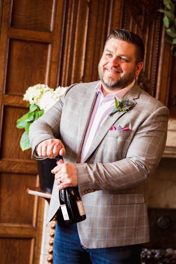 Candid shot of groom uncorking a champagne bottle at their Fairmont Banff Springs Hotel elopement