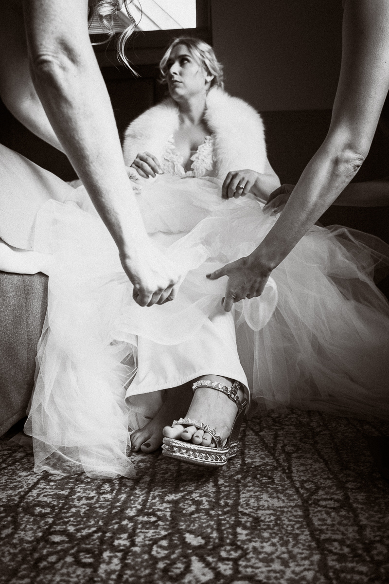 Artistic photo of bridesmaids helping bride get ready